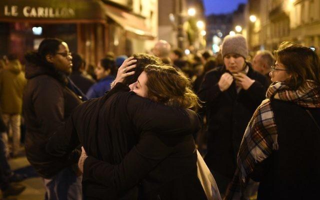 Rassemblement près du restaurant Le Carillon, l'un des sites des attentats à Paris, le 14 novembre 2015. Au moins 128 personnes ont été tuées dans les attentats de Paris qui ont eu lieu pendant la soirée du 13 novembre, avec 180 personnes blessées (Crédit : Martin Bureau/AFP)