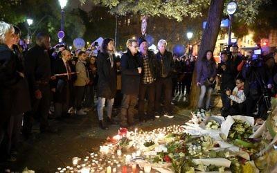 De Gauche à droite : Bono de U2, le guitariste The Edge, le batteur Larry Mullen Jr et le bassiste Adam Clayton rendant hommage aux victimes de attaques près de la salle de concert au Bataclan le 14 novembre 2015 Paris, un jour après une série de coordonnées attaques dans et autour de Paris (Crédit : AFP PHOTO / FRANCK FIFE)