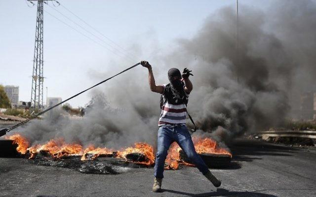 Un émeutier palestinien utilise un lance-pierre pour jeter des pierres vers les forces de sécurité israéliennes lors d'affrontements à Beit El, près de la ville cisjordanienne de Ramallah, le 11 octobre 2015 (Crédit : AFP / Abbas Momani)