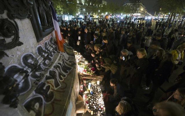 Des gens allument des bougies dans un mémorial de fortune en hommage aux victimes des attaques de Paris le 14 novembre 2015 au lieu sur la place de la République à Paris. les djihadistes de l'Etat Islamique ont revendiqué une série d'attaques coordonnées par des hommes armés et des kamikazes à Paris qui ont tué au moins 129 (Crédit : AFP PHOTO / JOEL SAGET)