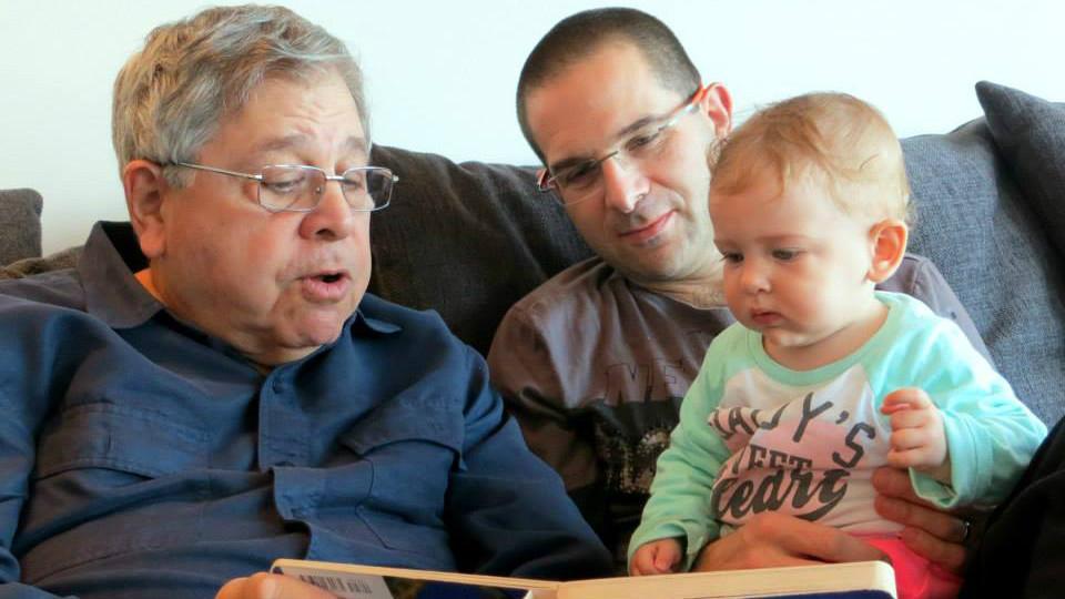 Richard Lakin (à gauche) lit un livre à sa petite-fille pendant que son fils Micah Avni regarde en janvier 2014 (Crédit : Autorisation)