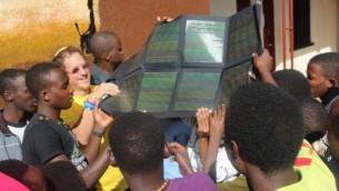 Abramowitz (à gauche) et des résidents du village de  jeunes Agahozo-Shalom tiennent un panneau solaire (Photo: Autorisation)