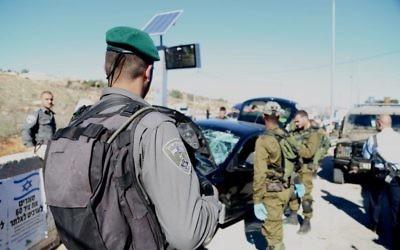 Garde-frontières et soldats israéliens sur les lieux d'une attaque à la voiture bélier au carrefour Tapuah, en Cisjordanie, le 24 novembre 2015. (Crédit : police israélienne)