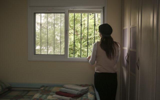 Une femme juive orthodoxe regarde par la fenêtre de sa chambre dans un refuge pour femmes victimes de violence à Beit Shemesh, le 15 juillet 2014 (Crédit : Hadas Parush / Flash90)