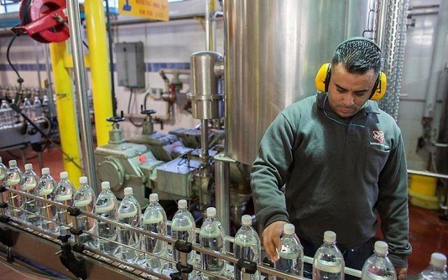 Les Palestiniens travaillent dans une usine Superdrink le 22 janvier 2015 au parc industriel de Atarot, en dehors de Jérusalem (Crédit : Yonatan Sindel / Flash90)