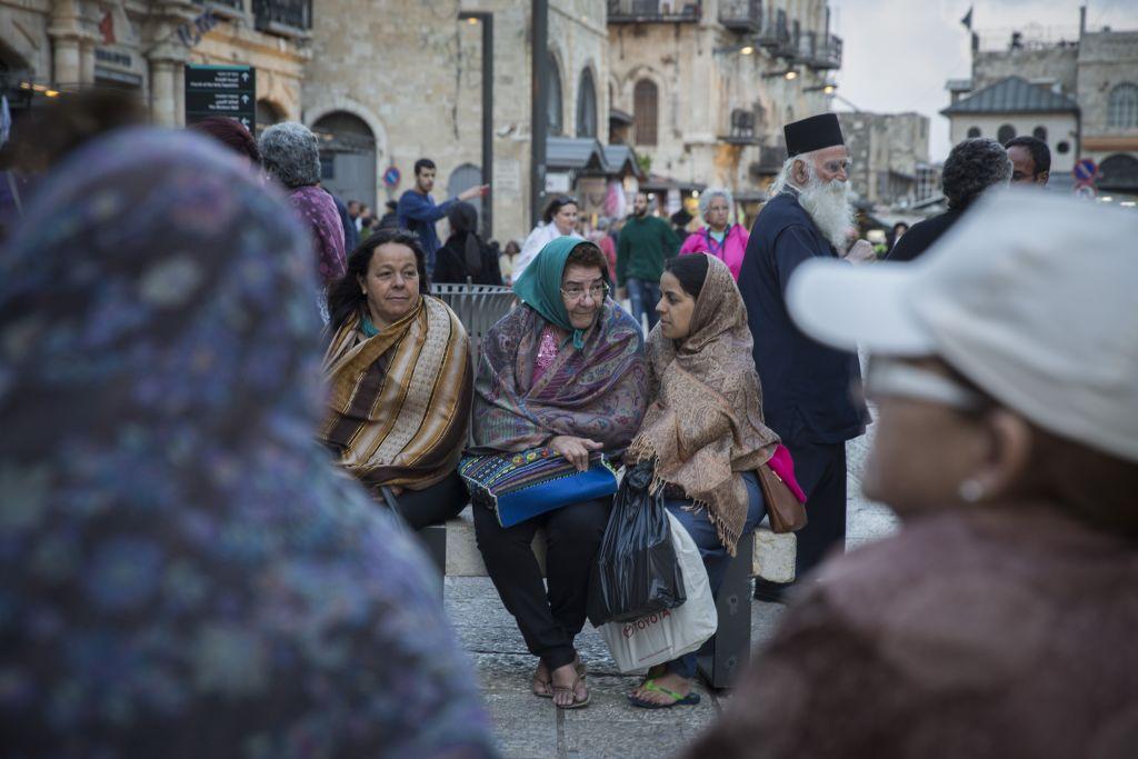 Les touristes se couvrent en attendant que leur groupe passe la porte de Jaffa dans la Vieille Ville de Jérusalem tandis que les températures commencent à baisser et l'hiver s'installe, le 28 octobre 2015 (Crédit : Hadas Parush / Flash90)