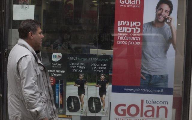 Un homme marchant à côté d'une affiche de publicité pour Golan Telecom à Jérusalem, le 5 novembre 2015 (Crédit : Lior Mizrahi / Flash90)