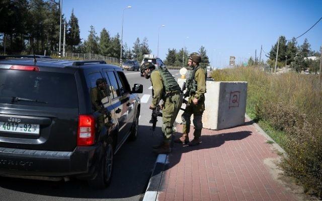 Des soldats de Tsahal inspectant un véhicule palestinien à un checkpoint temporaire mis en place près d'Alon Shvut, au Gush Etzion en Cisjordanie le 22 novembre 2015 (Crédit : Gershon Elinson / FLASH90)