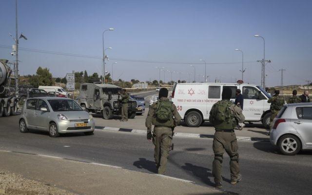 les forces de sécurité israéliennes à l'endroit où un chauffeur palestinien a percuté des soldats israéliens près de Beit umar, en cisjordanie, le 27 novembre, 2015 (Crédit :  Gershon Elinson / Flash90)
