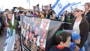 Des manifestants au Gush Etzion tenant une banderole representant des Israéliens tués dans des attentats terroristes, le 23 novembre 2015 (Photo: Ben Sales)