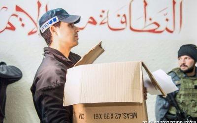 Un agent de police israélien participant à une perquisition dans les bureaux de la branche nord du Mouvement islamique  lundi 16 novembre 2015 (Crédit : Police israélienne)