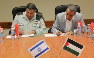"""Le ministre palestinien des affaires civiles, Hussein al-Sheikh, à droite, et le coordinateur israélien des activités gouvernementales dans les territoires (COGAT), le  Major Général, Yoav Mordechai, signent un """"mémorandum d'accord"""" qui pourrait ouvrir le service 3G dans les zones palestiniennes en trois à six mois, le 19 novembre 2015 (Crédit : IDF)"""