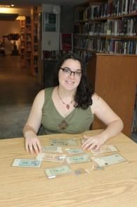 Marissa Natale étudie une nouvelle collection de monnaie de l'Holocauste pour l'université Clark et envisage comment les élèves peuvent être en mesure de l'utiliser (Crédit :  Autorisation de l'Université Clark)