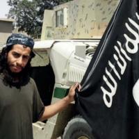 Abdelhamid Abaaoud, le cerveau présumé des attentats terroristes du 13 novembre à Paris, tenant un drapeau de l'Etat islamique dans cette image non datée d'un magazine publié par le groupe terroriste (Crédit : Capture d'écran)