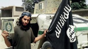 Abdelhamid Abaaoud, le cerveau présumé des attentats terroristes du 13 novembre à Paris, tenant un drapeau de l'Etat islamique dans cette image non datée d'un magazine publié par le groupe terroriste. (Capture d'écran)