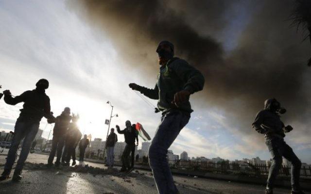 Palestiniens jettant des pierres sur les forces de sécurité israéliennes lors d'affrontements dans la ville palestinienne d'Al-Bireh à la périphérie de Ramallah, le 20 novembre 2015 (Crédit photo: Abbas Momani / AFP)