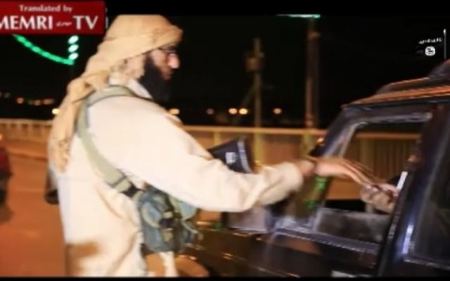 Un membre de l'EI distribue des bonbons à un conducteur de voiture pour célébrer le crash de l'avion russe dans le Sinai (Crédit : capture d'écran MEMRI)