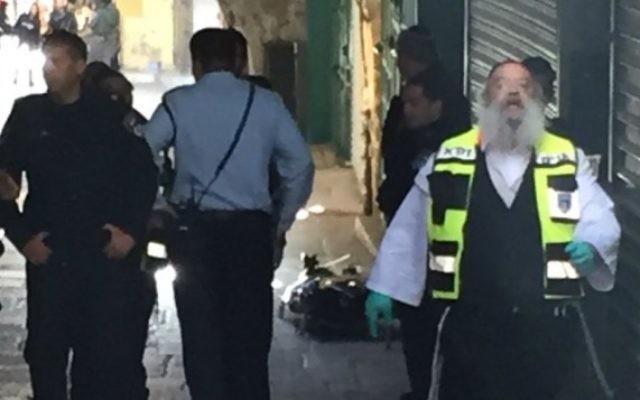 Policiers et secouristes sur le site où un terroriste palestinien a poignardé un agent de la police des frontières près de la porte de Damas, dans la Vieille Ville de Jérusalem le 29 novembre 2015. (Crédit : Police israélienne)