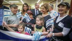 Le président de l'Agence juive, Nathan Sharansky et la ministre de l'Immigration et de l'Intégration d'alors Sofa Landver posant avec une famille arrivant de France en Israël en juillet 2014 (Crédit photo: David Salem)