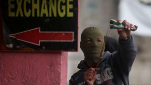 Un Palestinien utilise une fronde pour lancer des pierres sur les soldats israéliens lors d'affrontements dans la ville de Hébron en Cisjordanie, le 5 novembre 2015 (Crédit photo: Flash90)