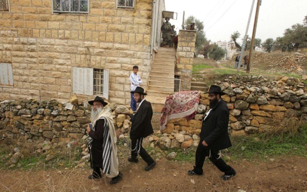 Des Juifs ultra-orthodoxes passent devant une maison palestinienne fouillée par des soldats israéliens dans la ville de Hébron en Cisjordanie, le 7 novembre 2015 (Crédit photo: Hazem Bader / AFP)