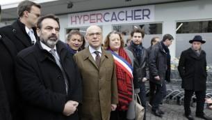 Le ministre français de l'Intérieur Bernard Cazeneuve (2e à partir de la gauche) et le président des consistoires Joel Mergui (à gauche)   le 15 mars 2015 devant le supermarché juif HyperCacher à Paris qui a été le site d'une prise d'otages sanglante lors d'une attaque djihadiste en janvier (Crédit photo: KENZO TRIBOUILLARD / AFP)