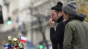 Le chanteur du groupe de rock américain Eagles of Death Metal, Jesse Hughes, (à guache) et le batteur Julian Dorio rendant hommage aux victimes des attentats du 13 novembre à Paris à un mémorial de fortune en face de la salle de concert du Bataclan à Paris le 8 décembre 2015 (Crédit : Miguel Medina / AFP)