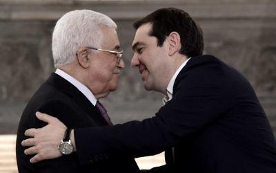 Le Premier ministre grec Alexis Tsipras (d) s'approche du président de l'Autorité palestinienne Mahmoud Abbas lors d'une conférence de presse après une réunion le 21 décembre 2015 à Athènes. (Crédit : ARIS MESSINIS / AFP)