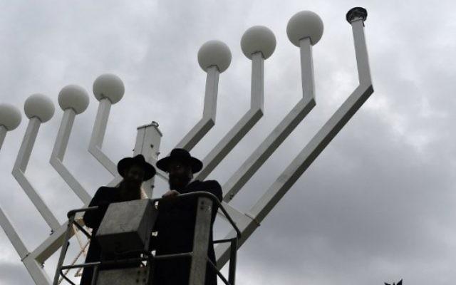 Deux rabbins se dressent sur une plate-forme surélevée où un géant candélabre de Hanoucca installé en face de la Porte de Brandebourg à Berlin le 4 décembre, 2015, deux jours avant le début de la fête juive de huit jours. (Crédit : AFP Photo / Tobias Schwarz)