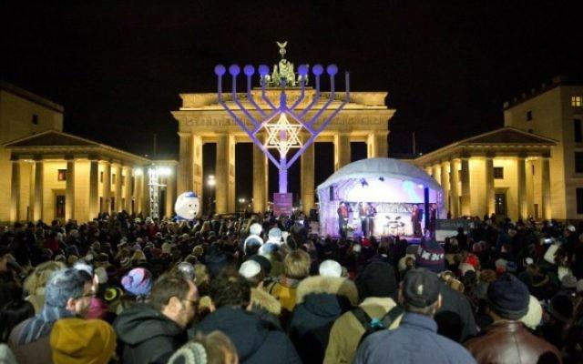 Les gens se tiennent devant un géant candélabre de Hanoucca en face de la Porte de Brandebourg à Berlin le 6 décembre 2015 au début de la fête juive de huit jours. (Crédit : AFP Photo / DPA / Jorg Carstensen)