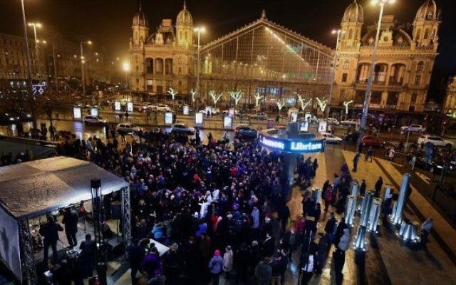 Célébrant Hanukkah, des gens dansent et chantent au Nyugati à Budapest, le 6 décembre 2015, le premier jour de la fête de huit jours. (Crédit : AFP Photo / Attila Kisbenedek)