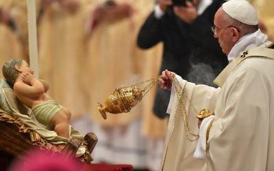 François balance un encensoir en face d'une statue de l'enfant Jésus, alors qu'il célèbre une messe la veille de Noël marquant la naissance de Jésus-Christ le 24 décembre 2015 à la basilique Saint-Pierre au Vatican.(Crédit :  AFP PHOTO / VINCENZO PINTO)