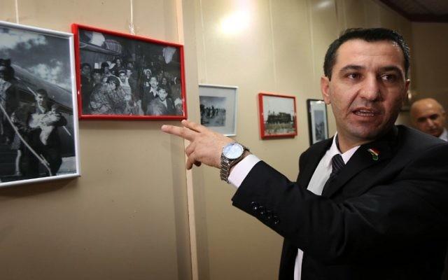 Sherzad Omar Mamsani, le représentant juif au ministère régional kurde, regarde les photos affichées lors d'une commémoration d'un pogrom des Juifs d'Irak datant de juin 1941, à Erbil, la capitale de la région autonome kurde du nord de l'Irak, le 30 novembre 2015. (Crédit : AFP / SAFIN HAMED)