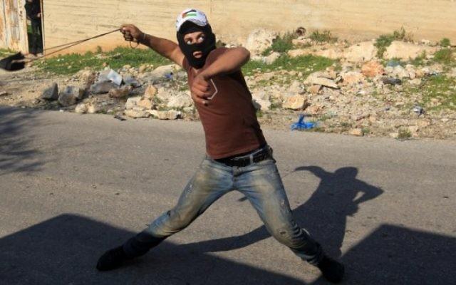 Un émeutier palestinien utilise une fronde pour lancer des pierres vers les forces de sécurité israéliennes lors d'affrontements près de Naplouse, le 11 décembre 2015. Illustration. (Crédit : AFP/Jaafar Ashtiyeh)
