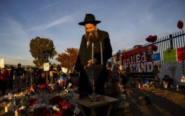 Rabbi Chalom Harlig se prépare à allumer la menorah pour la première nuit de Hanoukka à un mémorial de fortune situé près du Centre régional intérieure à la suite d'un tir de la terreur de masse qui a tué 14 personnes à San Bernardino, en Californie, le 6 décembre, 2015. (Crédit : AFP Photo / Patrick T. Fallon)