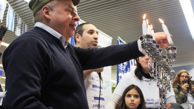 Le président de l'Agence juive, Nathan Sharansky rejoint la famille Ammar pour allumer la troisième bougie de Hanukka pendant une cérémonie d'accueil de dizaines d'immigrants juifs de France en Israël, le 8 décembre 2015. (Crédit : Nathan Roi/Agence juive pour Israël)