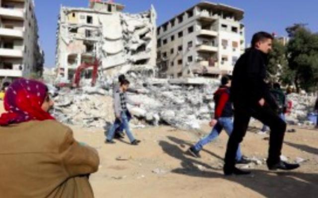 Des Syriens, le 20 décembre 2015, sur le site d'un raid aérien israélien présumé dans lequel le terroriste  Samir Kuntar aurait été abattu à Jaramana, au sud-est de la capitale syrienne Damas ( LOUAI BESHARA / AFP)