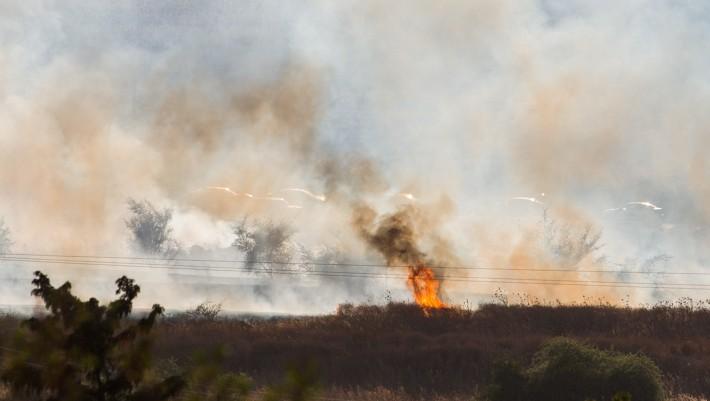 Un grand incendie qui fait rage près de Kfar Szold, causé par des missiles tirés depuis le côté syrien de la frontière israélo-syrienne dans les hauteurs du Golan dans le nord d'Israël le 20 août 2015 (Crédit : Basel Awidat / Flash90)