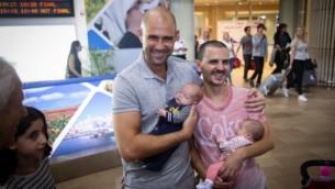 Le député du Likud Amir Ohana (à gauche) et son partenaire vu à l'aéroport international Ben Gourion de retour des États-Unis avec leurs bébés, le 26 septembre 2015. (Crédit : Flash90)