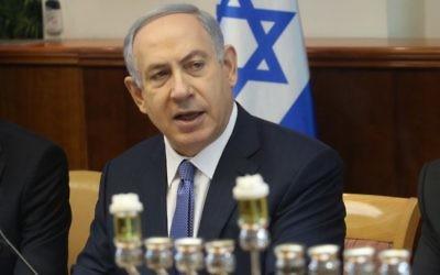 Le premier ministre Benjamin Netanyahu, au début de la réunion hebdomadaire du cabinet ministériel à Jérusalem, à côté d'une menorah prête pour le premier soir de la fête juive de Hanouka, 6 décembre 2015 (Crédit : Emil Salman/Haaretz)