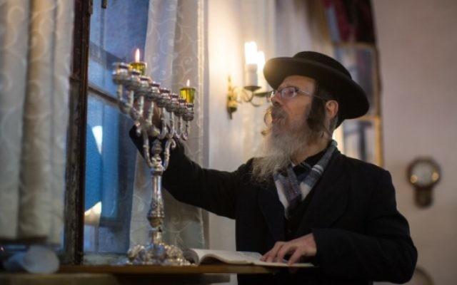 Un homme juif ultra-orthodoxe allume des bougies pour la fête juive de Hanoukka dans le quartier de Mea Shearim à Jérusalem le 6 décembre, 2015. (Yonatan Sindel / Flash90)