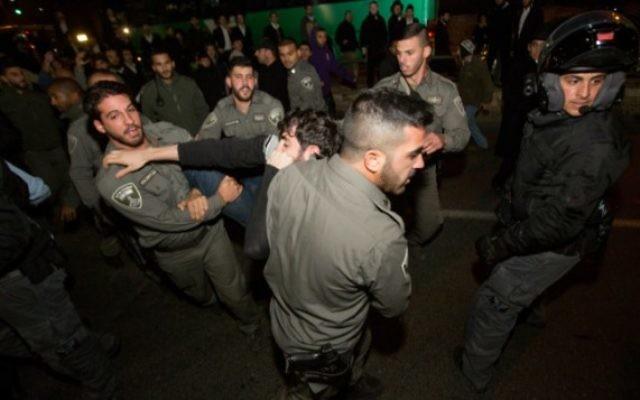 Des extrémistes juifs de droite et la police lors d'une manifestation contre l'arrestation de jeunes juifs soupçonnés d'être impliqués dans un incendie criminel dans le village cisjordanien de Duma, le 20 décembre 2015. (Crédit : Yonatan Sindel / Flash90)