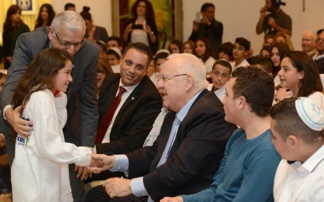 Le président Reuven Rivlin, au centre, accueille une jeune fille célébrant sa bat mitzvah à la résidence du président, à Jérusalem, le 21 décembre 2015 (Crédit : Mark Neiman / GPO)