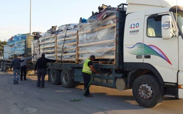 Un employé du ministère de la Défense découvre des plaques de blindage dans une cargaison de pièces de voiture en chemin vers la bande de Gaza par le terminal de Kerem Shalom le 29 décembre 2015 (Crédit : Ministère de la Défense)