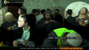 Le suspect principal de l'affaire Duma, entouré à gauche, prie sur le tombeau de Joseph aux côtés de Meir Ettinger, un autre extrémiste juif détenu par le Shin Bet (Crédit : capture d'écran Dixième chaîne)