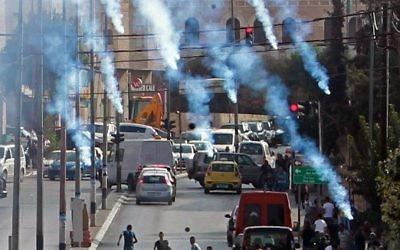 Des manifestants palestiniens se mettent à l'abri à du gaz lacrymogène lancé par les forces de sécurité israéliennes lors d'affrontements dans la ville de Bethléem en Cisjordanie, le 2 octobre 2015 (Crédit photo: Musa al Shaer / AFP)