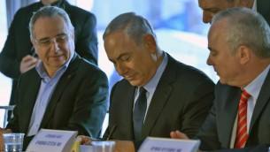 Le Premier ministre Benjamin Netanyahu (au centre) signe la clause 52 de la loi anti-trust pour approuver l'accord gazier, le 17 décembre 2015. (Crédit : Kobi Gidon / GPO)