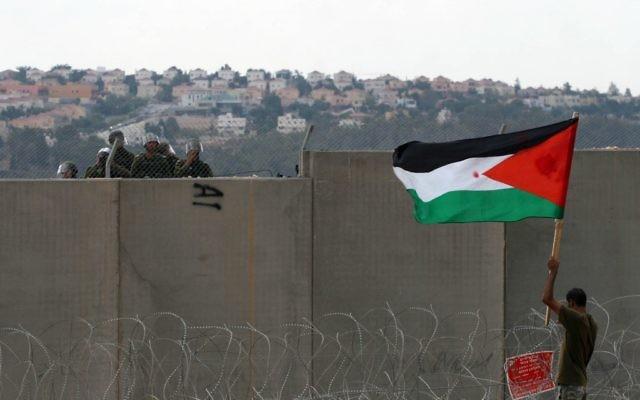 Un manifestant palestinien tient un drapeau, près de la clôture de sécurité à Bilin, en septembre 2011 (Crédit : Issam Rimawi/Flash90)