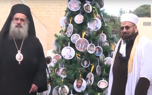 Les chefs religieux palestiniens posent devant un arbre de Noël avec des photos de martyrs palestiniens le 1er décembre 2015 (Crédit : YouTube / Al-Quds Educational Television)