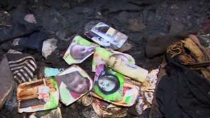 Les photos de famille dans les restes de la maison Dawabsha dans le village de Duma, en Cisjordanie, après l'attentat à la bombe incendiaire a priori menée par des extrémistes juifs le 31 juillet 2015. Le bébé de la famille a été tuée dans l'attaque et son père est mort de ses blessures huit jours plus tard, le 8 août 2015. (Crédit : capture d'écran YouTube)